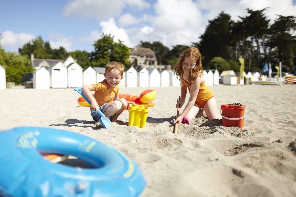Plage de Port Manec'h, Névez, les enfants sur la plage construisent des châteaux de sable, les cabines en bois blancs en arrière plan. Office de Tourisme de Concarneau à Pont-Aven, Crédit Alexandre Lamoureux